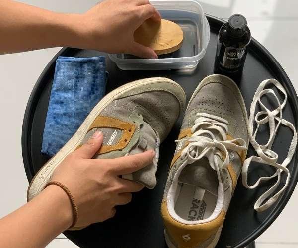 Nhúng bàn chải vào dung dịch vệ sinh giày